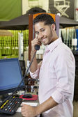 Portrait of a happy salesperson listening to telephone receiver in store — Stock Photo