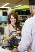 Portrait of a happy young woman paying through credit card in store — Stockfoto