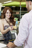 Beautiful young woman paying through credit card in store — Stock Photo