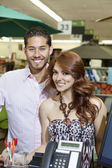 Portrait of a happy couple standing in store — Stock Photo