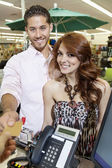 Portrait of a happy couple paying through credit card — Stock Photo