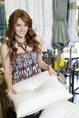 Portrait of beautiful young woman shopping for cushion in store — Stock Photo