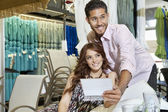 Happy young couple looking away in store — Stock Photo