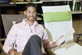 Retrato de un hombre feliz sentado en la silla en la tienda — Foto de Stock