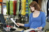 Beautiful young woman looking a paper while selecting textile sample in store — Stock Photo
