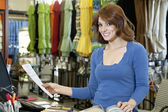 Portrait of beautiful young woman with paper and textile samples standing in store — Stock Photo