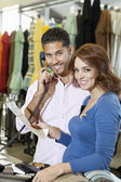Portrait of a happy couple with man with telephone receiver and woman with paper in store — Stock Photo