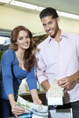 Portrait of young couple with textile samples in store — Stock Photo