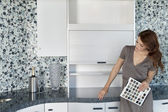 Beautiful young woman with color samples looking at contemporary kitchen cabinets — Stock Photo