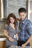 Beautiful young couple looking at color samples in model home — Stock Photo