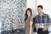 Portrait of beautiful young couple with color samples standing in model home kitchen — Stock Photo
