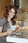 Portrait of a happy young woman with tile samples in model home — Stock Photo