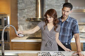 Young couple looking at sink faucet on kitchen counter in model home — Stock Photo