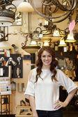 Retrato de mujer joven hermosa parada en la tienda de luces — Foto de Stock