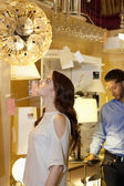 Beautiful young woman looking at lighting fixture hanging while man browsing in background — Stock Photo