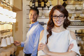 Portrait of a happy woman wearing glasses with arms crossed while man looking in background — Stock Photo