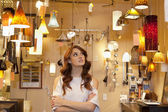 Beautiful young woman browsing for lights with arms crossed in store — Stock Photo