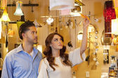 Young couple looking at price tag of lighting equipment in lights store — Stock Photo