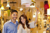 Portrait of young couple with price tag in lights store — Stockfoto