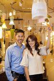 Retrato de um jovem casal feliz com tag de preço em luzes armazenar — Foto Stock