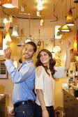 Vista lateral do jovem casal dançando de costas em luzes armazenar — Foto Stock