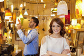 Portrait of young woman with arms crossed while man looking at price tag in background in lights store — Stock Photo