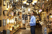 Happy young man browsing for lights fixture in store — Stock Photo