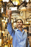 Happy young man looking at price tag of chandelier in lights store — Stock Photo