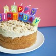 Close-up of birthday candles on torte cake over colored background — Stock Photo #21900061