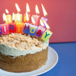 Close-up of candles burning on birthday cake over colored background — Stock Photo