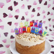 Close-up of birthday cake with candles over heart shaped background — Stock Photo
