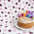 Close-up of birthday candles on cake over heart shaped background — Stock Photo