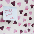 Stock Photo: Close-up of sticky note with message over heart shaped wall