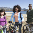 Multiethnic Friends With Mountain Bikes By The Lake - Stock Photo