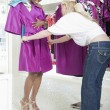 Assistant Helps Woman Consider Fuschia Raincoat — Stock Photo #21900497