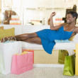 Woman Lies With Shopping Bags In Store Seating Area - Stock Photo