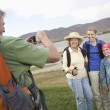 Stock Photo: Man Photographs Mother, Daughter And Granddaughter Lakeside