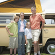 Family Of Four Standing By Campervan - Stock Photo
