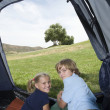 Stock Photo: Happy Brother And Sister Lying In Tent
