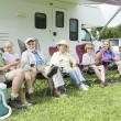Family Sitting Outside RV Home - Stock Photo