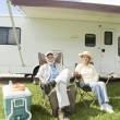 Stock Photo: Senior Couple Sit Outside RV Home