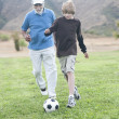 Grandfather And Grandson Playing Football On Field — Stock Photo