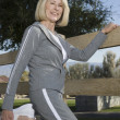 Mature Woman Stretches Leg In Warm Up Exercise - Stockfoto