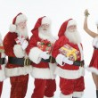 Stock Photo: Men Dressed In SantClaus Outfits With Mrs. Claus Holding Mistletoe