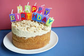 Close-up of birthday candles on torte cake over colored background — Stock Photo