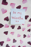 Close-up of sticky note with a orthographic message over heart shaped background — Stock Photo