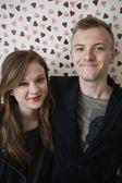 ハート形の壁紙笑みを浮かべて美しい若いカップルの肖像画 — ストック写真