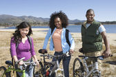 Multiethnic Friends With Mountain Bikes By The Lake — Stock Photo