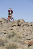 Man Stands With Mountain Bike On Rocky Outcrop — Stock Photo