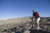 Man With Mountain Bike In An Arid Landscape — Stock Photo